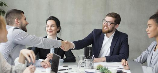 Two people shaking hands during a meeting